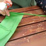 Enrollaremos papel de seda verde alrededor del palillo de madera. Nos ayudaremos con el pegamento.